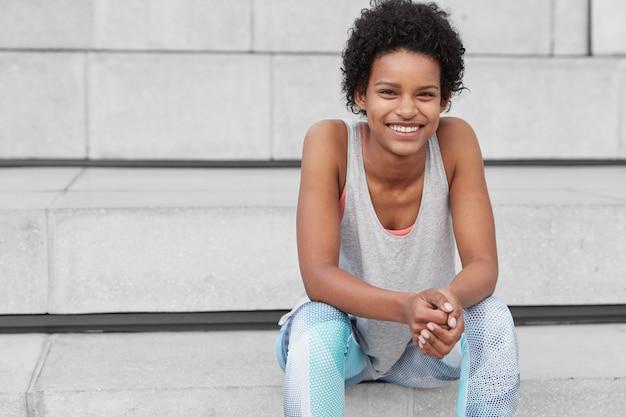 Vue horizontale de la femme à la peau sombre et heureuse détendue avec une coupe de cheveux bouclée, a un sourire à pleines dents, montre des dents blanches, étant en bonne forme comme le sport tous les jours, se repose dans les escaliers de la ville avec un espace libre