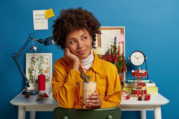 Vue horizontale d'une femme pensive vêtue d'une veste jaune, détient un cocktail de lait de poule, aime boire de délicieux punch au lait d'oeuf crémeux