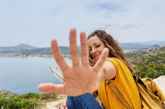 Vue horizontale d'une femme tendant la main vers la caméra. concept de la côte espagnole blanche. heureuse femme voyageant.