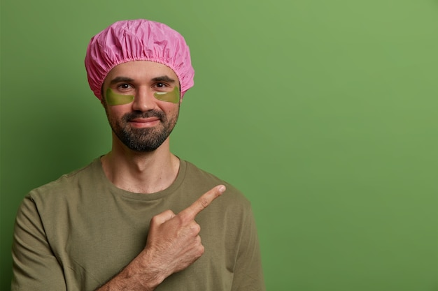 Vue horizontale de l'homme mal rasé satisfait porte un chapeau de bain rose, un t-shirt décontracté, un traitement de la peau des yeux, applique des tampons de collagène pour réduire les ridules, pointe sur un espace vide, fait la publicité d'un produit
