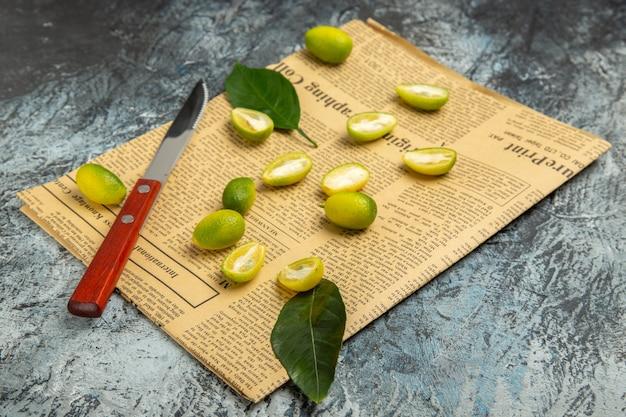 Vue horizontale des kumquats frais coupés en deux sur des journaux sur fond gris