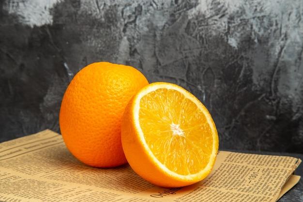 Vue horizontale d'oranges fraîches sous forme coupée et entière sur papier journal sur fond gris