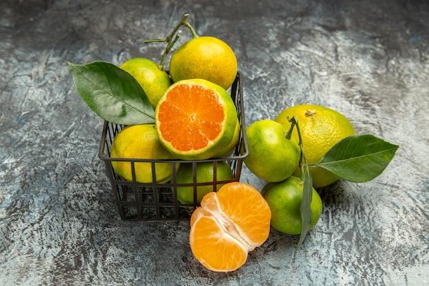 Vue horizontale d'un panier plein de mandarines vertes fraîches et coupées en deux et de mandarines pelées sur fond gris