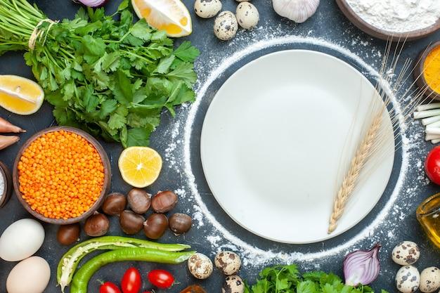 Vue horizontale de la préparation du dîner avec des œufs, des légumes frais, des paquets verts sur bleu foncé