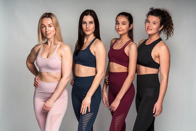 Vue horizontale des quatre femmes avec un corps et une ethnie différents posant ensemble pour montrer l'apparence de la femme. concept de sport et de loisirs