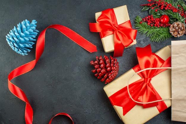 Vue horizontale d'un rouleau de cônes de conifères ruban rouge et de branches de sapin cadeau sur table sombre