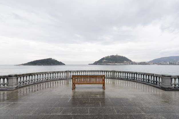 Vue horizontale d'un seul banc sur un point de vue depuis une plage de la concha, espagne