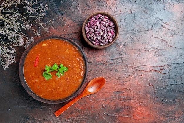 Vue horizontale de la soupe aux tomates classique dans un bol brun haricots et cuillère sur table de couleurs mélangées