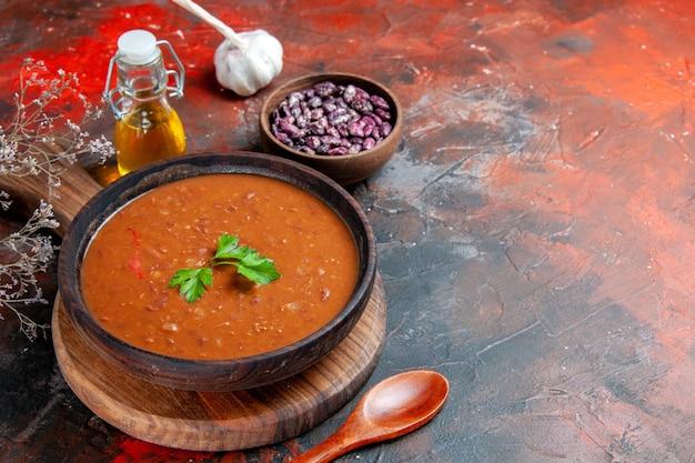 Vue horizontale de la soupe aux tomates sur une planche à découper brune et une bouteille d'huile sur une table de couleurs mélangées
