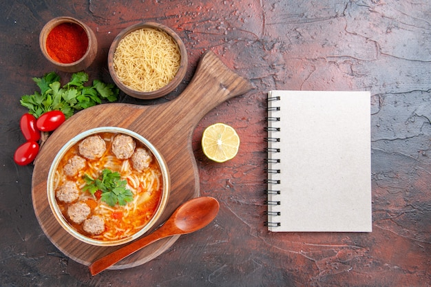Vue horizontale de la soupe de boulettes de viande à la tomate avec des nouilles dans un bol marron différentes épices et cahier sur fond sombre