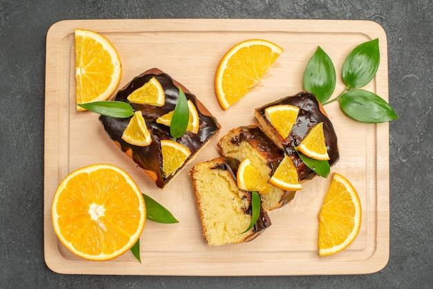 Vue horizontale des tranches de citron et des tranches de gâteau hachées sur table sombre
