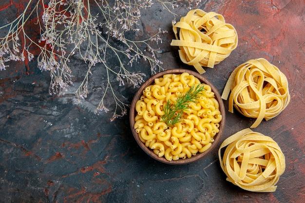 Vue horizontale de trois portions non cuites de spaghettis et pâtes papillon dans un bol brun et vert sur table de couleurs mixtes