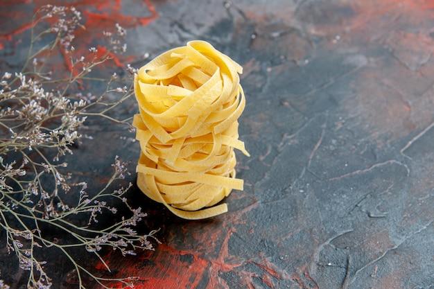 Vue horizontale de trois portions de spaghettis empilés sur table de couleurs mixtes