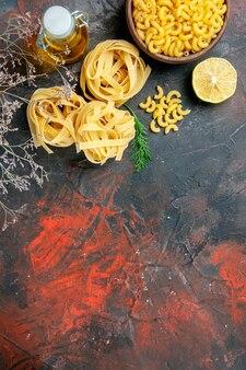 Vue horizontale de trois portions de spaghettis non cuits et bouteille d'huile verte sur le dessus de la table de couleurs mélangées