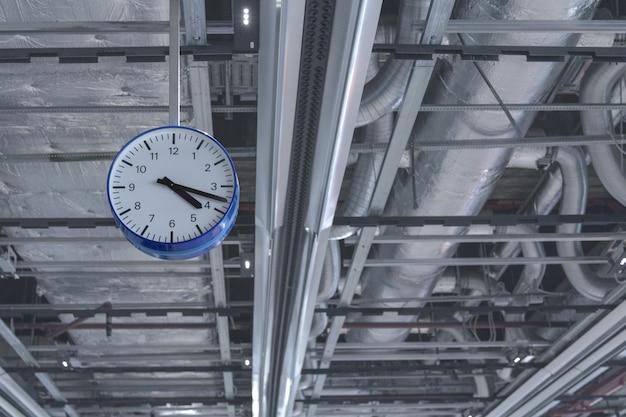 Vue de l'horloge suspendue au plafond contre les tuyaux de ventilation.