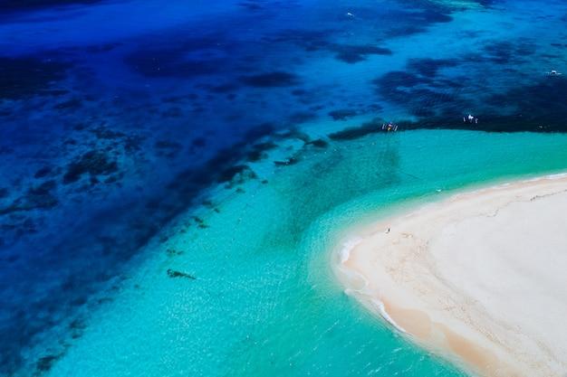 Vue sur l'île de daku depuis le ciel. homme relaxant en prenant un bain de soleil sur la plage. prise de vue avec drone au-dessus de la belle scène. concept sur les voyages, la nature et les paysages marins