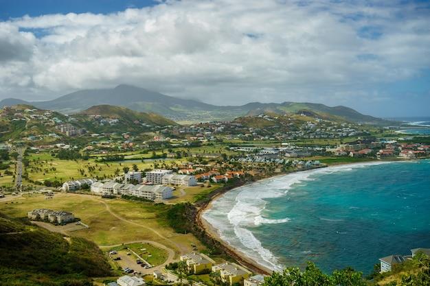 Une vue sur l'île de saint-kitts avec quartier résidentiel et plage au premier plan et collines verdoyantes