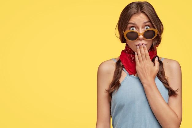 Vue de l'image de la femme aux cheveux noirs surpris couvre la bouche avec la main, porte des nuances à la mode, bandana rouge, regarde avec des yeux éclatés