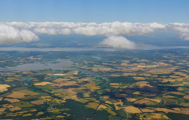 Vue imprenable avion au-dessus de cumulus nuages moelleux panoramiques la terre champs d'herbe verte forêts ciel bleu