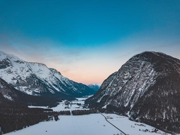 Vue imprenable sur une chaîne de montagnes dans une journée froide et neigeuse au coucher du soleil