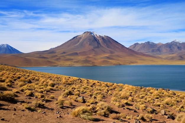 Vue imprenable sur le lac miscanti de couleur bleu profond avec la montagne de cerro miscanti en arrière-plan, chili