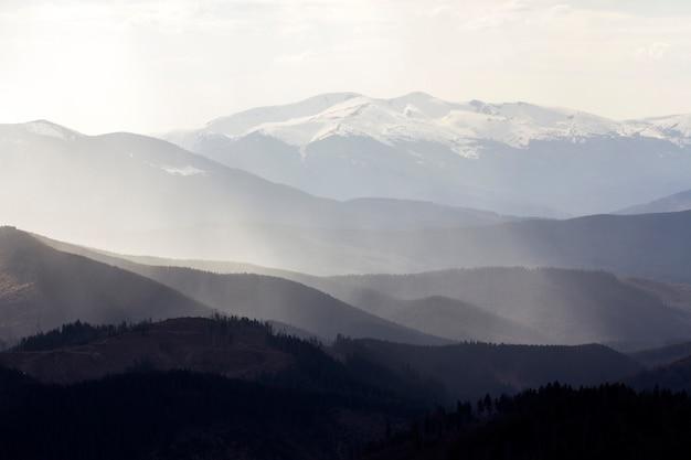 Vue imprenable sur les magnifiques montagnes des carpates brumeuses, couvertes de forêt toujours verte sur un matin ou un soir calme et brumeux sous un ciel nuageux sombre. cimes des montagnes couvertes de neige au loin.