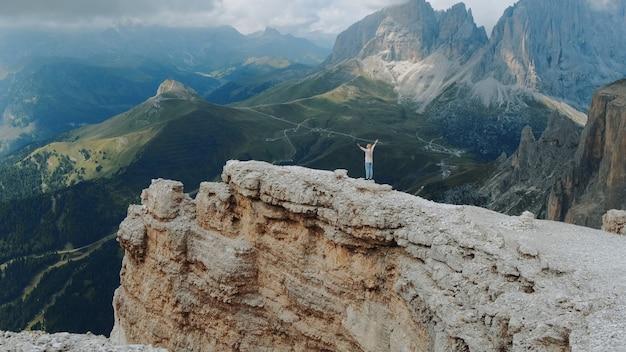 Vue imprenable sur les montagnes avec une femme debout sur le dessus avec les mains tendues. sentir la liberté et profiter de la nature.