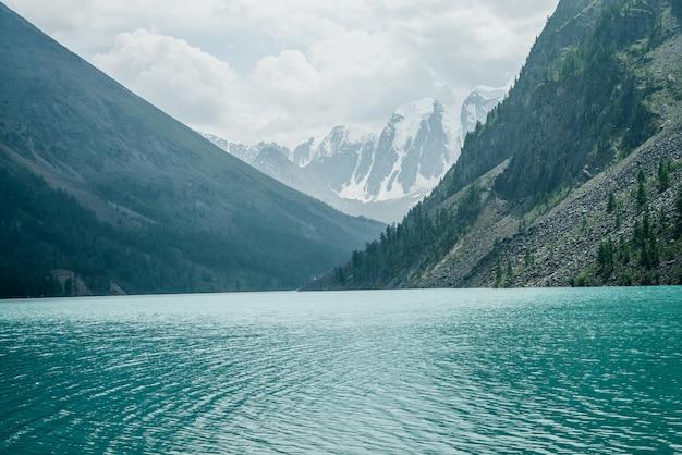 Vue imprenable sur les ondulations méditatives sur l'eau calme et claire azur du lac de montagne