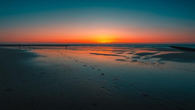 Vue imprenable sur le reflet du coucher de soleil dans l'océan à domburg, pays-bas