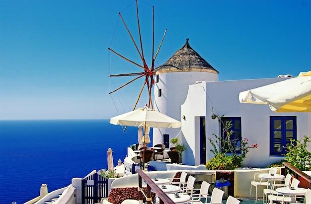 Une vue imprenable sur santorin. la plus belle île d'europe. moulins à vent traditionnels dans le village d'oia. voyage en grèce