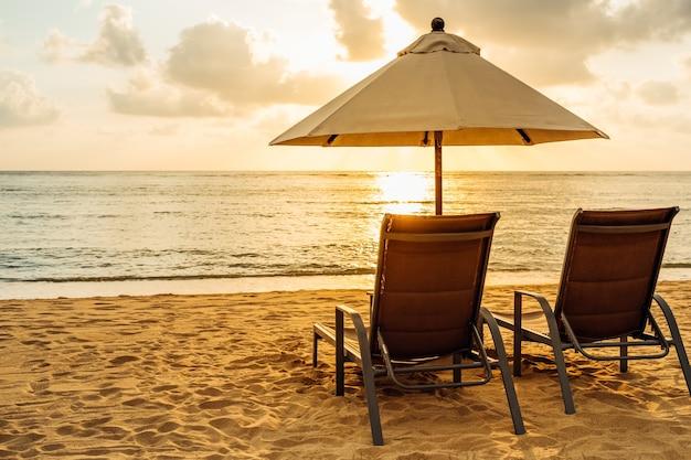 Vue imprenable sur les transats et le parasol en fin de soirée d'été dans un beau coucher de soleil