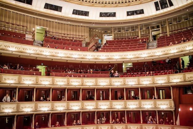 Vue de l'intérieur de l'auditorium de l'opéra national de vienne avec le public sur les balcons avant de commencer la représentation à vienne, en autriche.