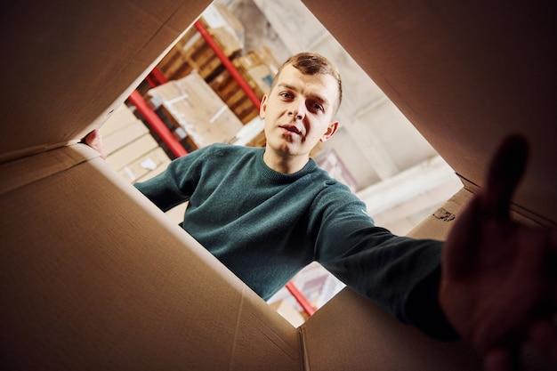 Vue de l'intérieur de la boîte en papier. l'homme en vêtements décontractés regarde vers le bas et essaie d'atteindre la caméra à la main.