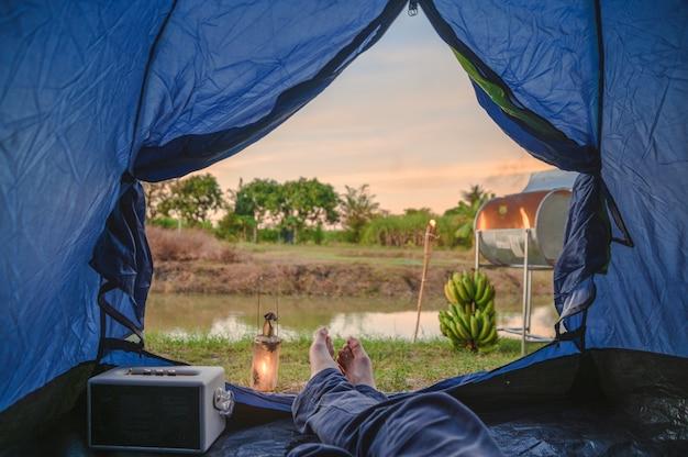 Vue de l'intérieur de la tente avec détente et feu de camp près du marais