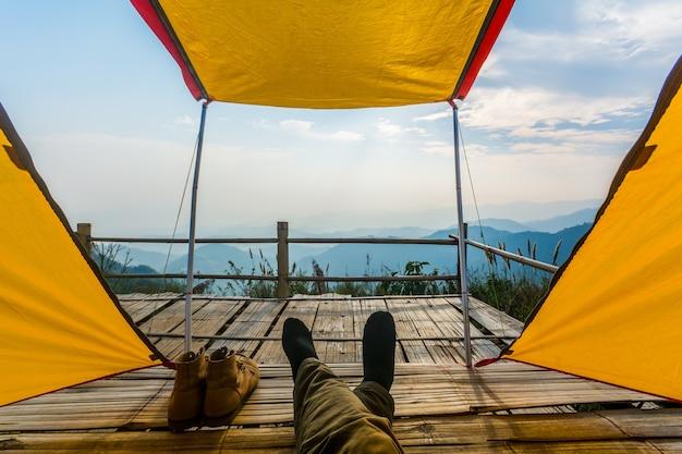 Vue de l'intérieur d'une tente à la forêt et les jambes des hommes émergent de la tente.