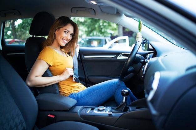 Vue intérieure de voiture de femme pilote mettant la ceinture de sécurité