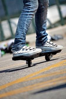 Vue des jambes d'une jeune femme adepte du street-surf faisant des mouvements.