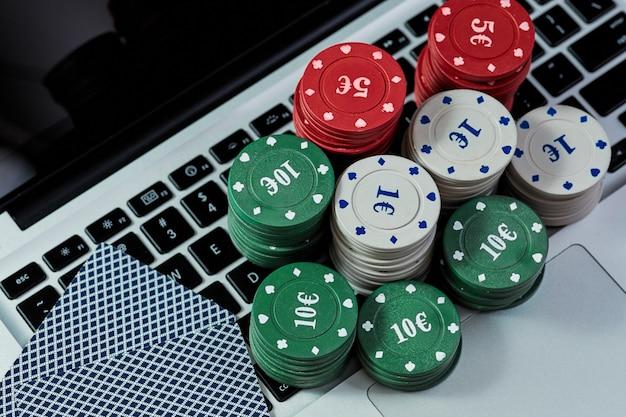 Vue des jetons et des cartes de casino sur un ordinateur portable pour jouer en ligne. concept de jeu en ligne, poker, casino virtuel.
