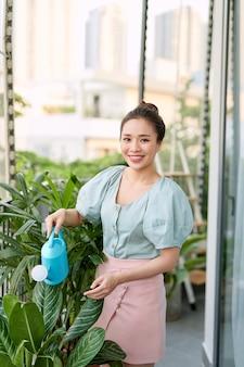 Vue d'une jeune femme arrosant le jardin sur son jardin balcon
