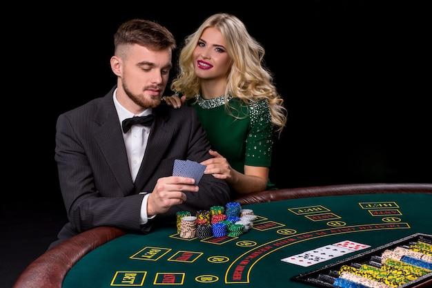 Vue d'un jeune homme confiant avec la dame pendant qu'il joue au poker. la blonde regarde la caméra et sourit