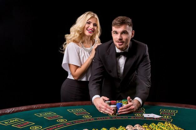 Vue d'un jeune homme confiant avec la dame pendant qu'il joue au poker. ils regardent tous les deux la caméra et sourient
