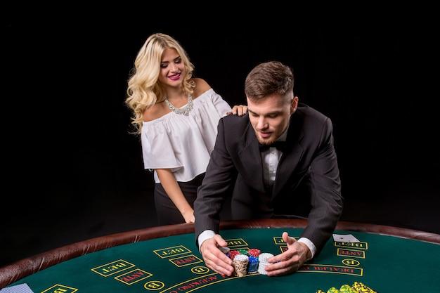 Vue d'un jeune homme confiant avec la dame pendant qu'il joue au poker.