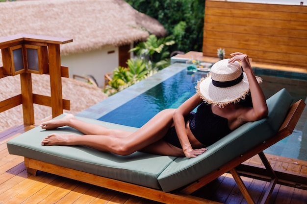 Vue de la jolie femme bronzée en bikini vintage noir se trouve sur un lit de soleil vert à la villa incroyable à la journée ensoleillée, se reposer, profiter de vacances
