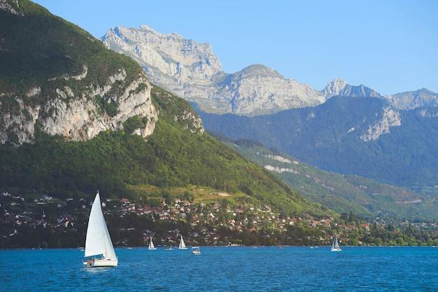 Vue sur le lac d'annecy aux eaux turquoises claires, bateaux à voile et maisons traditionnelles en bois en journée d'été, france