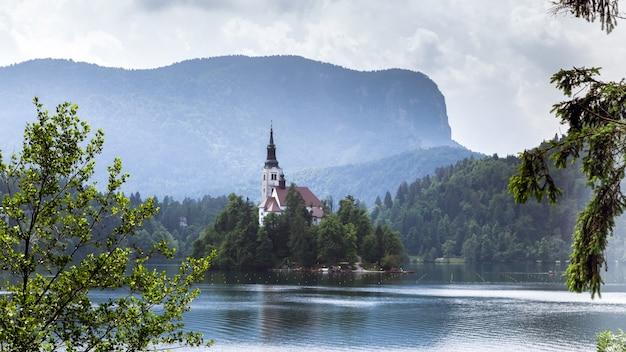 Vue sur le lac de bled île de bled avec petite église de pèlerinage montagnes en arrière-plan la slovénie