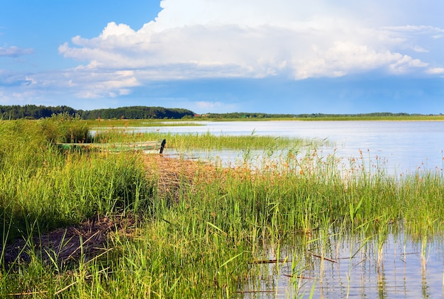 Vue sur le lac en été avec bateau en bois près du rivage
