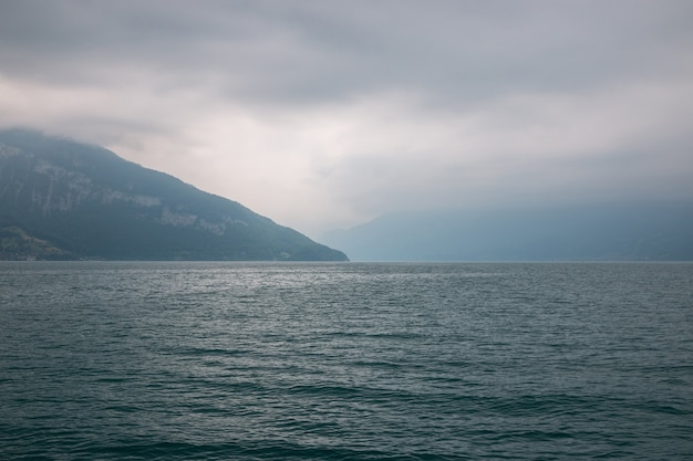 Vue sur le lac de thoune et les montagnes du navire dans la ville de spiez, suisse, europe. paysage d'été. scène dramatique de nuages bleus maussades