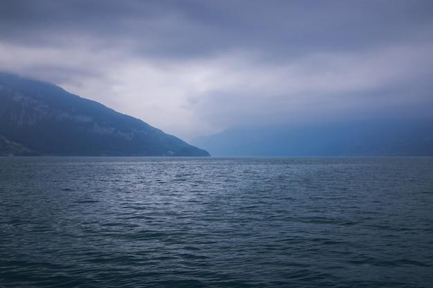 Vue sur le lac de thoune et les montagnes du navire dans la ville de spiez, suisse, europe. scène dramatique de nuages bleus maussades