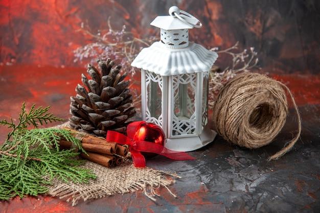 Vue latérale d'accessoires de décoration cône de conifère une boule de corde et sapin brances limes cannelle sur fond sombre