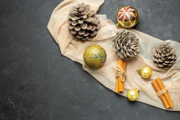 Vue latérale d'accessoires de décoration de limes à la cannelle et de trois cônes de conifères sur une serviette de couleur nude sur fond de couleur noire